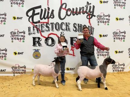 man and girl pose with sheep