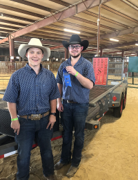 teen boys in cowboy hats pose with blue ribbon