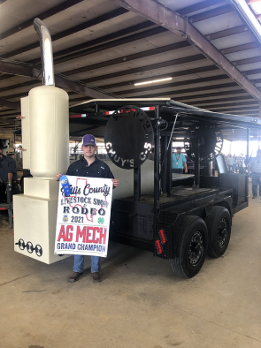 boy poses with smoker trailer he made