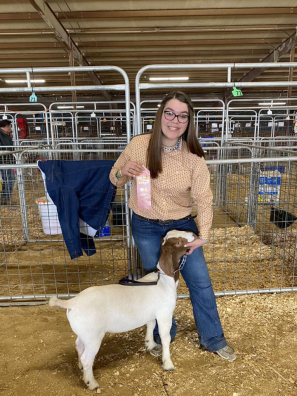 teen girl poses with goat and a pink ribbon