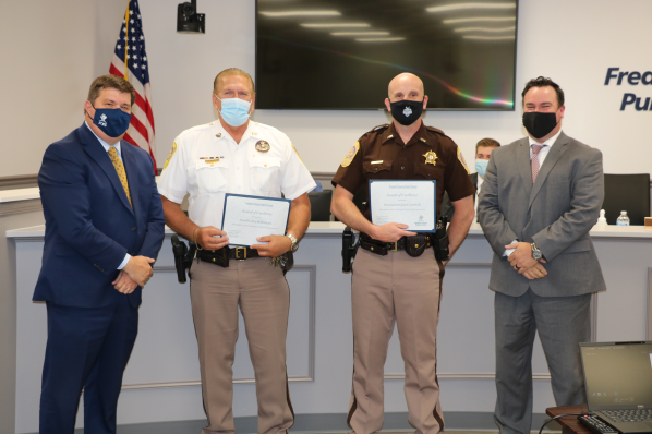 Dr. Sovine and Jay Foreman present certificates to Sheriff Millholland and First Lt. Cornwell
