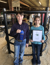 boy and girl pose with awards